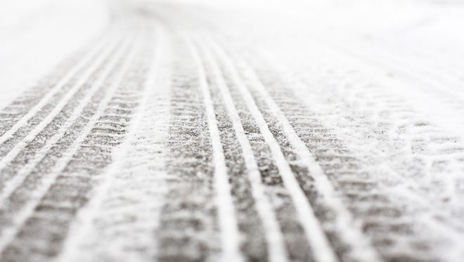 Wheel tracks on the road covered with snow.