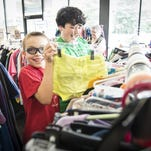 At left, Daniel Rosborough, 10, and Bradley Mabry, 11, cut up at Kiwanis Thrift Store in Black Mountain, where many parents shop for school clothes.