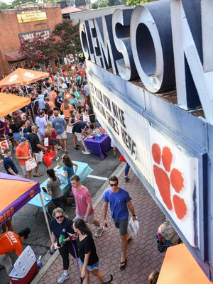 Students and visitors walk during the Clemson University Welcome Back Festival in downtown Clemson on Wednesday. A blocked off section of College Avenue had 70 booths with food, prizes, and merchandise helping raise money for the Student Alumni Council Endowment Scholarship Fund.