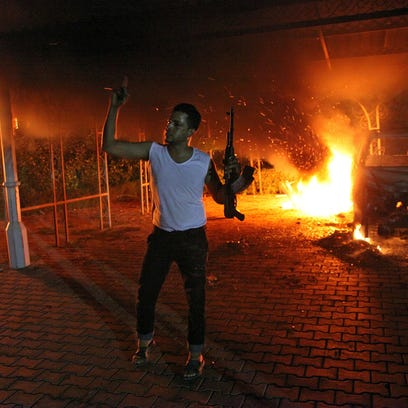 A man waves his rifle as buildings and cars are engulfed