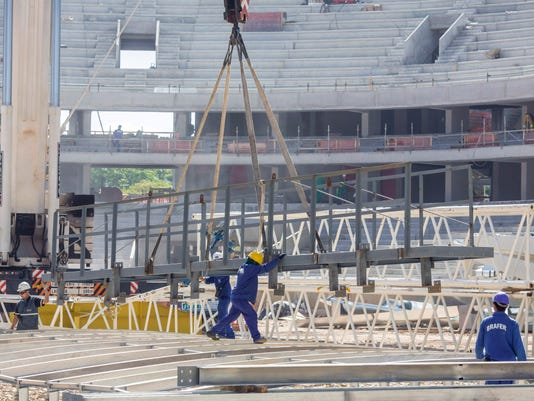 In this Dec. 4, 2013 photo released by Portal da Copa, personnel continue construction on the Arena da Baixada stadium in Curitiba, Brazil. Brazilian authorities said on Wednesday, Jan. 29, 2014 that the pace of construction has improved at this delayed World Cup stadium and are optimistic the city will still be able to host games. FIFA said local officials have until Feb. 18, 2014 to show the city will be able to finish the stadium in time and football's governing body will make its own evaluation to decide whether to keep games in Curitiba. (AP Photo/Alexandre Carnieri, Portal da Copa)