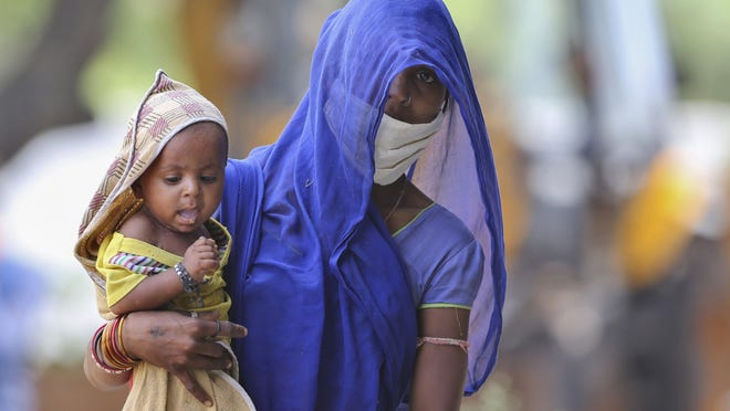 An Indian migrant woman from Madhya Pradesh state carries her child and waits at a temporary shelter to register for free travel on a train, during lockdown to prevent the spread of new coronavirus on the outskirts of Hyderabad, in the southern Indian state of Maharashtra, Saturday, May 16, 2020. Tens of thousands of migrant laborers have been returning from big cities to their villages after losing jobs because of a countrywide lockdown imposed in late March to contain the spread of the coronavirus.