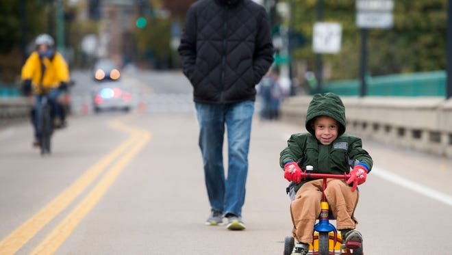 Prentice Elliott and son Avery cross the Gay St. Bridge during Open Streets on Sunday, October 29, 2017.