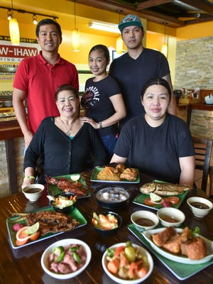 The Calalo family, led by Tess Calalo, front left, unites at their family restaurant, Nayon Express in Harmon, on Feb. 9.