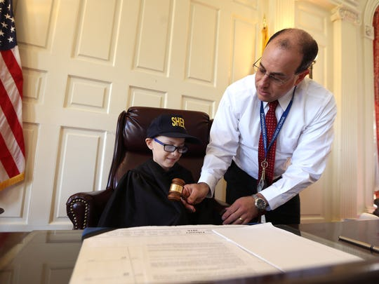 Superior Court Assignment Judge Stuart Minkowitz gives Ethan Geller, 7, the gavel in his courtroom as Ethan is honored as 'hero for a day' by the Morris County Sheriff's Office. Atlantic Health Systems/Goryeb Children's Center and the Sheriff's Office collaborated in showing Ethan around the courthouse and sheriff's office. June 24, 2016, Morristown, NJ