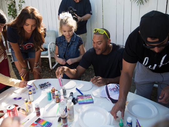 Boston Red Sox player, Chris Dominguez, center, paints with Lily Hixenbaugh,8,  along with Red Sox player, Deven Marrero, right, at Valerie's House in Fort Myers.  Several players gathered at the house to brighten the day of kids who are grieving the loss of parents or siblings.
