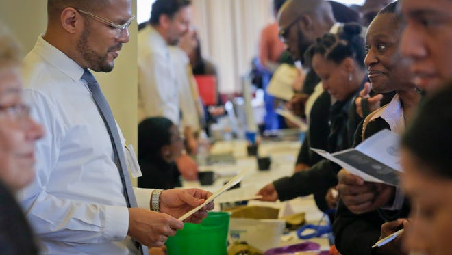 Johnnie Davis, a representative for New York's Business Integrity Commission, reviews a resume during the city's Department of Citywide Administrative Services 2016 job fair. U.S. employers added a decent 161,000 jobs in October 2016 and raised pay sharply for many workers.