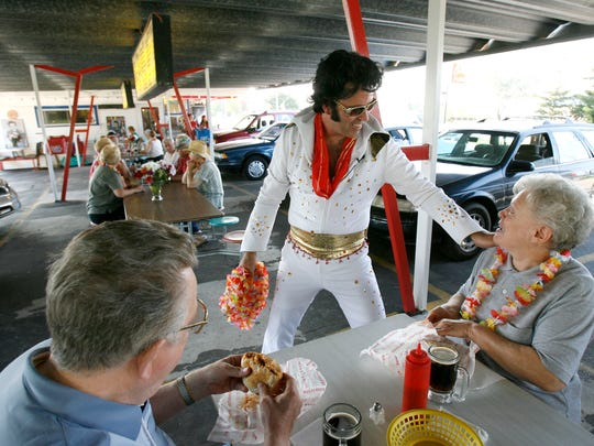 Dressed as Elvis, owner Carl Mann has fun interacting with Sonja and Mardy Boyum of New London at Charlie's Drive-In Restaurant in Hortonville in this Aug. 12, 2009, photo.