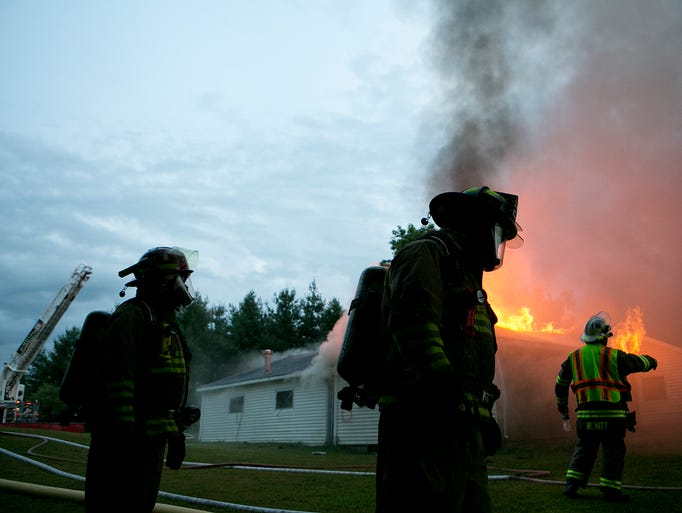 """Volunteer firefighters look on as a controlled fire burns during training on Mann Street in the town of McMillian, Monday, Aug. 18, 2014. Volunteer fire departments from the towns of Auburndale, Cameron, Hewitt, Lincoln, McMillian, Rudolph, and Stratford held a training session for new volunteer firefighters to feel a fire for the first time in a controlled situation. Town of McMillian fire captain Kevin Schmidtke said, """"There is nothing closer to it then the real thing. This allows rookies to see what it takes to run a scene."""""""