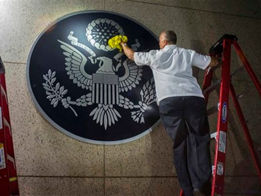 A worker wipes a representation of the The Great Seal of the United States at the the newly opened U.S. Embassy in Havana, Cuba, Friday, Aug. 14, 2015.