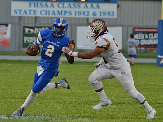 Titusville quarterback OC Brothers sprints out of the pocket after being pressured by Astronauts Ralph Lawrence Friday night in Titusville. (photo by Tony Dees/Florida Today)
