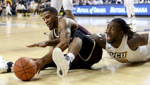 ULM's Marcus Washington, left, and VCU's Mo Alie-Cox fight for the ball during the second half of an NCAA college basketball game in Richmond, Va.