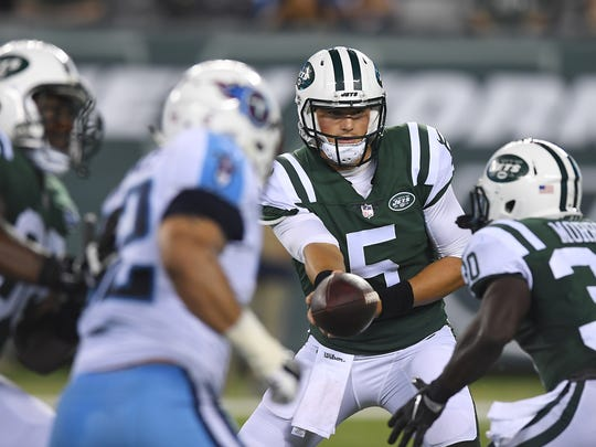 Jets Christian Hackenberg (5) hands the ball off in