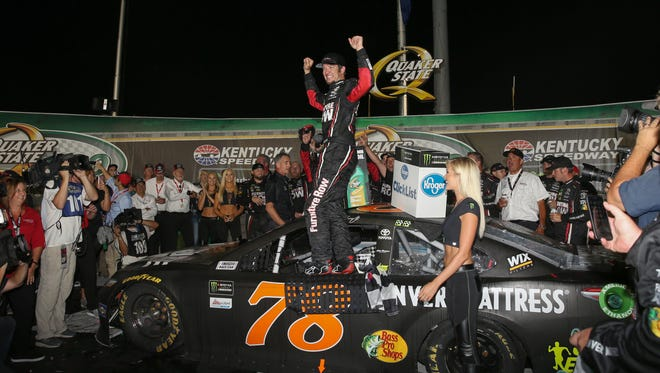 Monster Energy NASCAR Cup Series driver Martin Truex Jr. (78) celebrates after winning the Monster Energy NASCAR Cup Series Quaker State 400 auto race, Saturday, July 8, 2017, at the Kentucky Speedway in Sparta, Ky. (The Cincinnati Enquirer/Kareem Elgazzar)