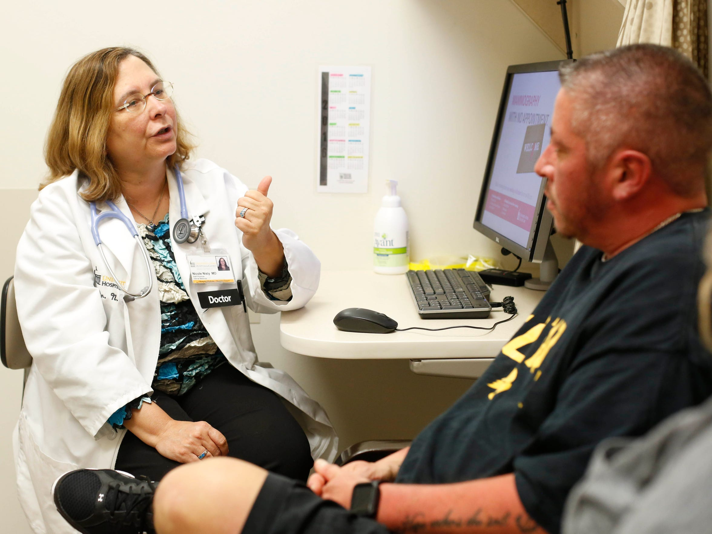 Dr. Nicole Nisly, left, talks with Aiden DeLathower about his testosterone dosage Wednesday, Oct. 19, 2016, at the University of Iowa LGBTQ Clinic in Iowa City. DeLathower credits the clinic with getting him the appropriate dose as he transitioned from female to male.