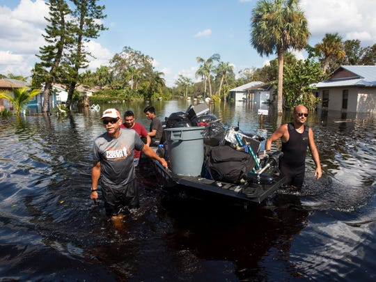 Don Manley, left, and Pedro Castellano, right, pull Manley's boat, loaded with resident's belongings, along a flooded Chapman Avenue in Bonita Springs on Friday, Sept. 15, 2017, five days after Hurricane Irma. #weareonenation