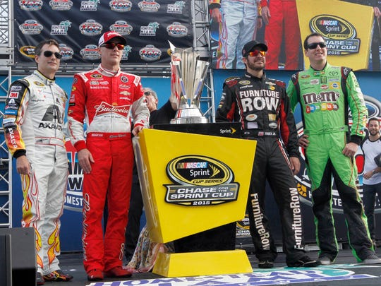 Jeff Gordon, Kevin Harvick, Martin Truex Jr., and Kyle Busch, from left, pose with the trophy for photographers during driver introductions at the NASCAR Sprint Cup Series auto race, Sunday, Nov. 22, 2015, at Homestead-Miami Speedway in Homestead, Fla.