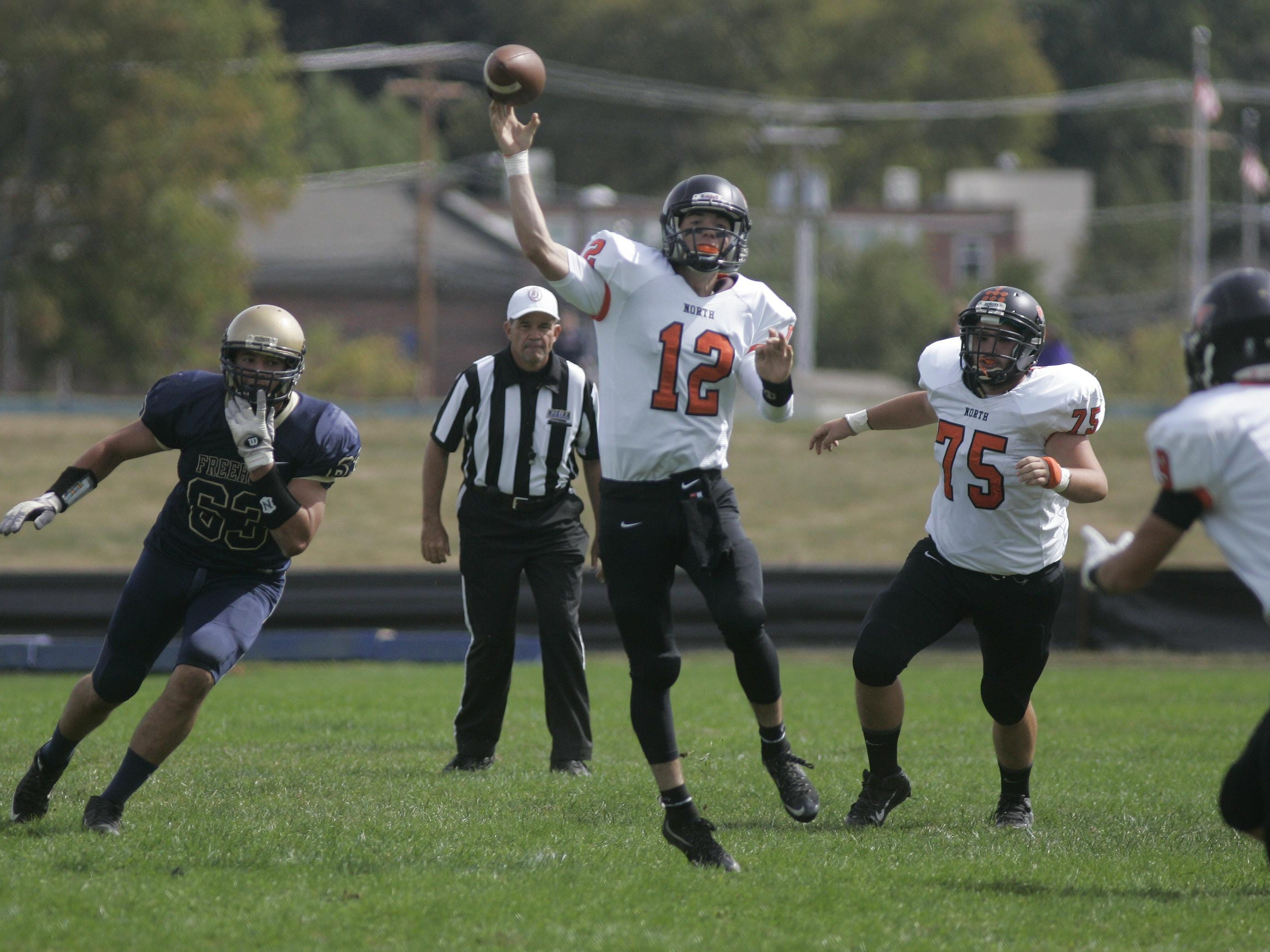 Middletown North High School quarterback Donald Glenn launches a pass against Freehold's defense during a Shore Conference game, Saturday afternoon, at Freehold.