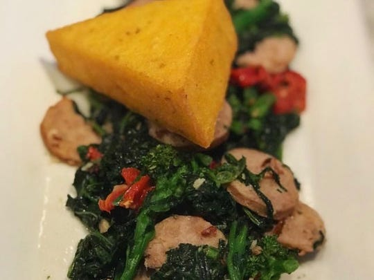 A triangle of polenta is served on a bed of broccoli rabe and sausage and peppers at LaScala's Birra.