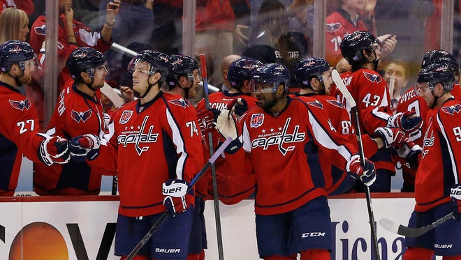 Oct 29, 2014: Washington Capitals center Evgeny Kuznetsov (92) celebrates with teammates after scoring a goal against the Detroit Red Wings in the second period at Verizon Center.
