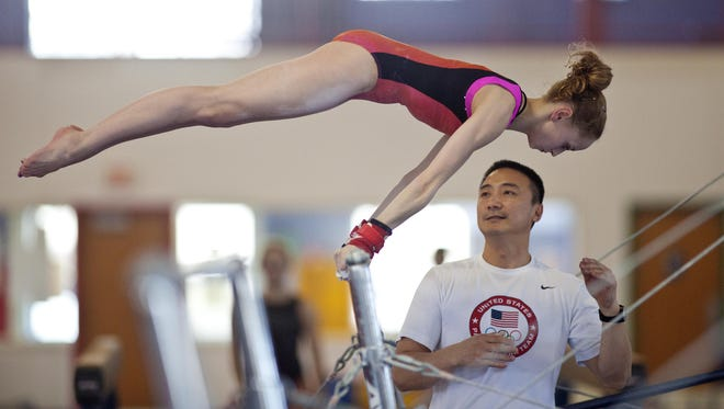 Rachel Gowey's breakout season is already over. The 16-year-old gymnast from Johnston, above, broke her right ankle after landing short on her beam dismount during training Wednesday at the U.S. Gymnastics Championships. Gowey pitched forward and immediately fell to her knees, grabbing her right ankle. Gowey appeared to be in tears as coach Liang Chow, pictured below, carried her off the podium.
