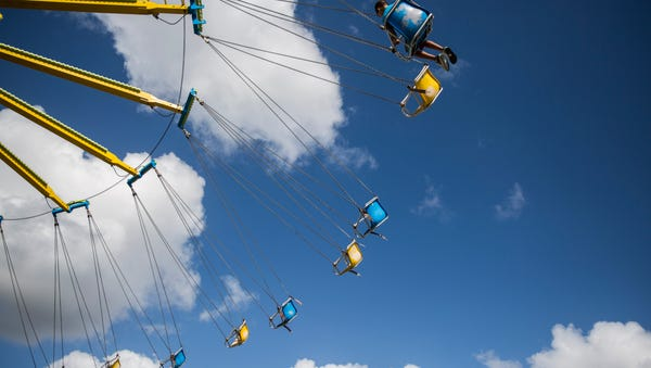 Michael Price, 8, rides the chair swings in the...