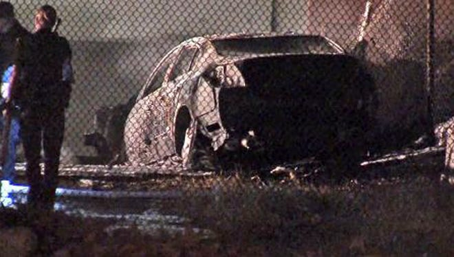 This image taken from video provided by ABC-TV shows officials at the site of a fiery single-vehicle crash that killed 5 people in Burbank, Calif.