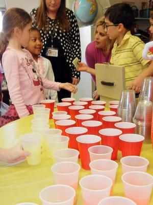 Wedgwood first-graders Taymiyyah Abdul-Rahman (left) and Hannah Gallinaro pay second-grader Sawyer Quallen for their lemonade.