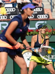 Martina Hingis, of Switzerland, and Sania Mirza, of India, return serve to the Russian pair of Elena Vesnina and Ekaterina Makanrova during the BNP Paribas Open Women's Doubles final.
