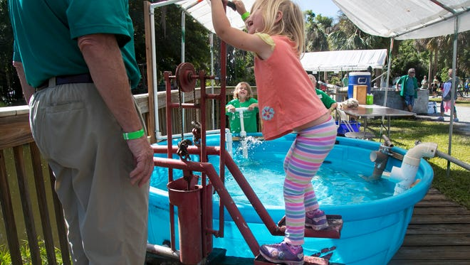 Ellie Flood, 4, front, and her sister Ivy Flood, 6, pump water using different kinds of pumps at ECHO's Global Food and Farm Festival on Saturday in North Fort Myers.