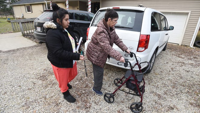 Direct support aid Monica Rivera helps Susan Harmon to a van for a trip into town. Harmon lives in a residential home for people with developmental disabilities in Coshocton.