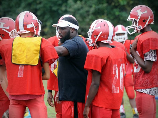 Laurel head coach Eston Ennis talks with his players during a Bulldogs' practice in Laurel on Tuesday, Sept. 27, 2016.