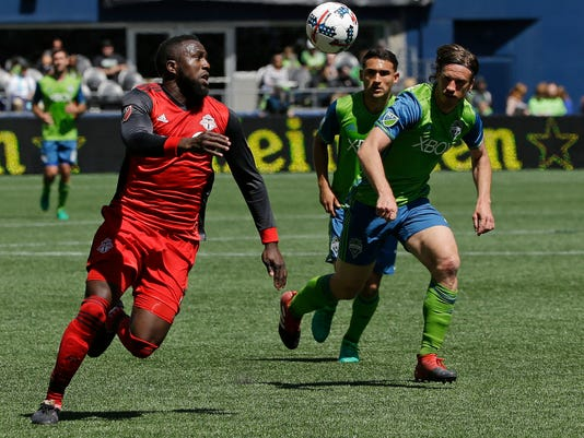 Toronto FC forward Jozy Altidore, left, chases down the ball as Seattle Sounders defender Gustav Svensson, right, and Cristian Roldan, center, look on during the first half of an MLS soccer match, Saturday, May 6, 2017, in Seattle. (AP Photo/Ted S. Warren)