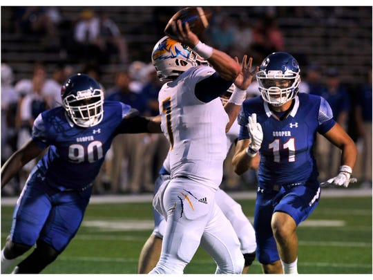 Cooper High School defensive lineman Michaelin Toney (left) and linebacker Justin Wright close in on Frenship High School quarterback Austin Phillips during Friday's game at Shotwell Stadium Sept. 22, 2107. Cooper won, 62-3.
