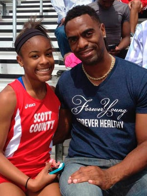 In this May 3, 2014, file photo, Trinity Gay, a seventh-grader racing for her Scott County High School team, poses for a photo with her father, Tyson Gay, after she won the 100 meters and was part of the winning 4-by-100 and 4-by-200 relays at the meet in Georgetown, Ky.