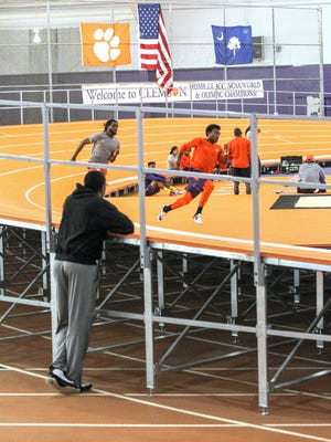 Life coach Bryan Narcisse, left, watches Dareyus Person, left, and Cordell Lamb, right, practice the 400 meter run around the bank of a new track inside the Clemson University Indoor Track/Field Facility. The new track is built over the old track.