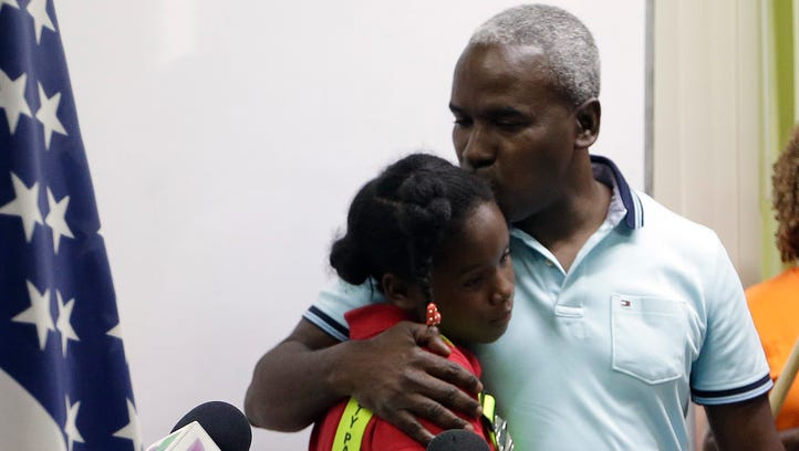 Rony Ponthieux, right, hugs his daughter Ronyde Christina
