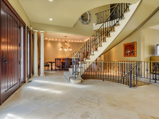 The foyer features custom mahogany doors and a floating brass staircase to the second floor.