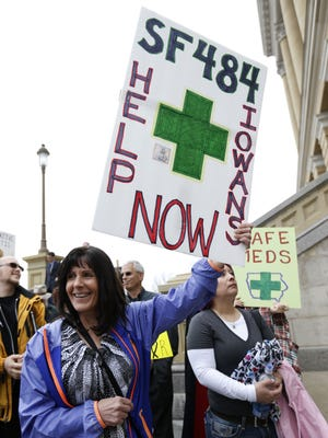 Lori Ersland of Belmond, left, displays a sign showing her support for medical marijuana in Iowa. Advocates rallied at the Statehouse in Des Moines on April 7.