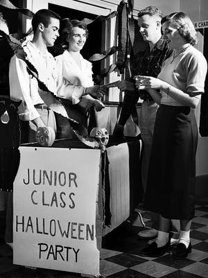 October 17, 1953 - Selling first tickets on October 17, 1953, to the Junior Class All Student Halloween Party set for October 30 at Memphis State College are (from left) Johnny Avgeris of 206 Exchange and Pat Wilkinson of 3220 Spottswood, class officers. Receiving tickets, which will help finance a class project for the college are Bruce Graves of 1789 Mignon and Betty Jo Reding of 1029 Stonewall.