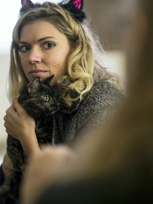 Kacy Hess, foreground, communications director at the Humane Society of Lebanon County, listens to Cynthia Harner, a pet psychic, as she does a reading for Nina, a cat who is the longest resident at the society's shelter. The society held its second annual Howl-o-ween adopt-a-thon at the Jackson Township shelter.