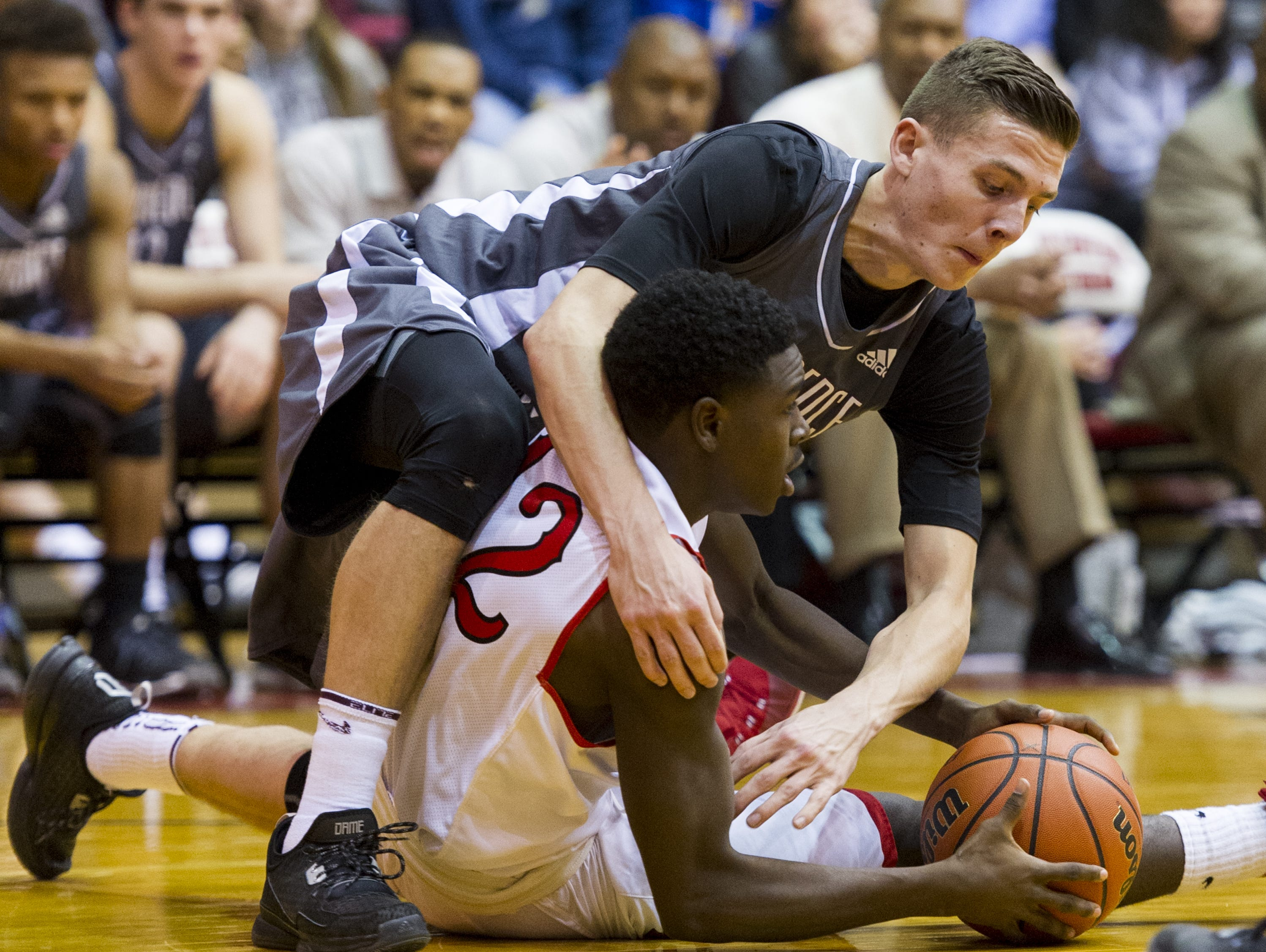 Lawrence Central High School senior Kyle Guy (24) goes after a loose ball against North Central High School sophomore Donald Johnson (12) during the first half of action in an IHSAA high school boys basketball game at North Central High School, Tuesday, Jan. 12, 2016.