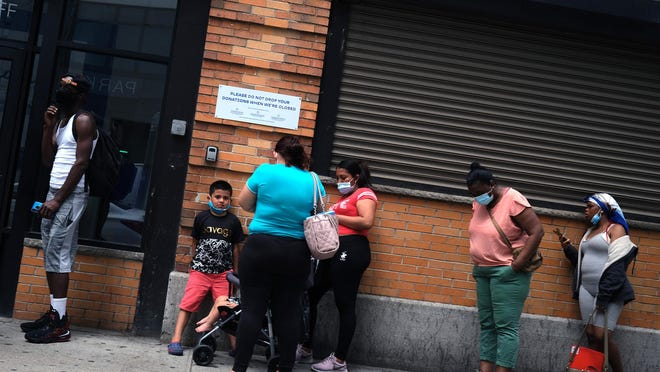 People wait in line for food assistance cards on July 7, 2020 in the Brooklyn borough of New York City.