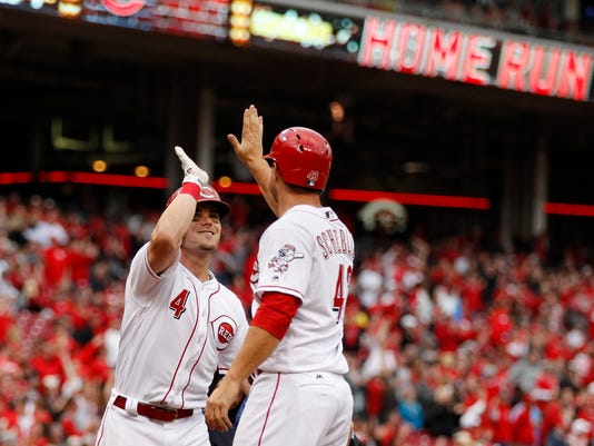Cincinnati Reds' Scooter Gennett (4) celebrates with Scott Schebler, center, after hitting a two-run home run off Philadelphia Phillies relief pitcher Jeanmar Gomez in the ninth inning of a baseball game, Monday, April 3, 2017, in Cincinnati. (AP Photo/Gary Landers)