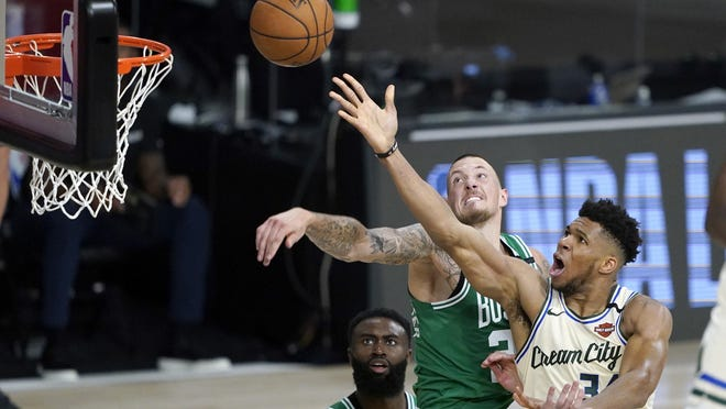 Milwaukee's Giannis Antetokounmpo, right, drives past the Celtics' Daniel Theis during Friday's return to game action in Lake Buena Vista, Fla. Antetokounmpo scored 36 points and grabbed 15 rebounds in the Bucks' 119-112 win.