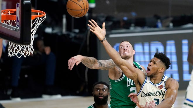 Milwaukee Bucks' Giannis Antetokounmpo, right, heads to the basket as Boston Celtics' Daniel Theis defends during the second half of an NBA basketball game Friday, July 31, 2020, in Lake Buena Vista, Fla.