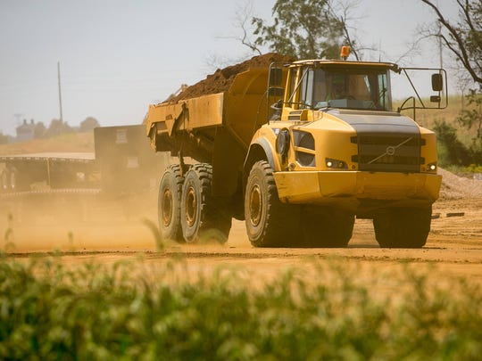 Dirt flies through the air as a construction truck rolls along at the U.S. 301 construction site in Middletown next to the Spring Arbor community. Work started in March.