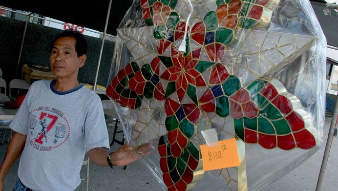Venefredo Borbon holds onto a parol, a Christmas lantern made in the Philippines, as wind blows it around at a stand set up on the old Ben Franklin parking lot. The stand selling the parols was set up Nov. 19-20 by the Filipino Community.