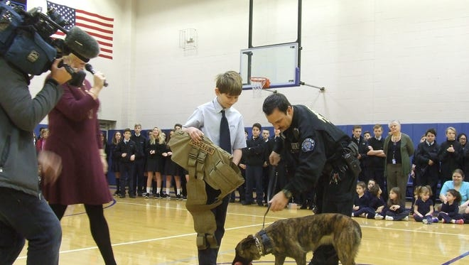 Aidan Harris, with tie, raised money to buy a bulletproof vest for Trexx, the Highland Park Police Department dog. He presented the vest to Trexx and her human  partner, Officer Chris Zuellig, during an assembly at St. Michael's Catholic School on Friday.