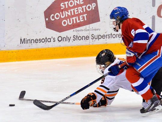 St. Cloud Tech's Brad Amundson (9) falls to the ice